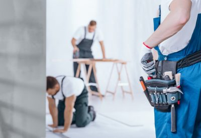 Close-up of handyman wearing gloves and tool belt on blue trousers during home renovation